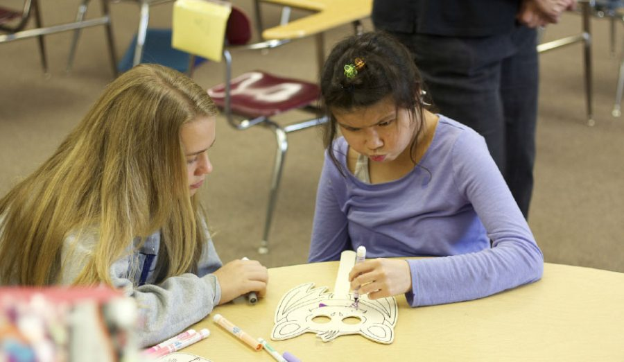 Leadership student Caitlin Willard, left, works with sophomore Erika Reed.  Students in the program work on several different arts and crafts projects on every visit.