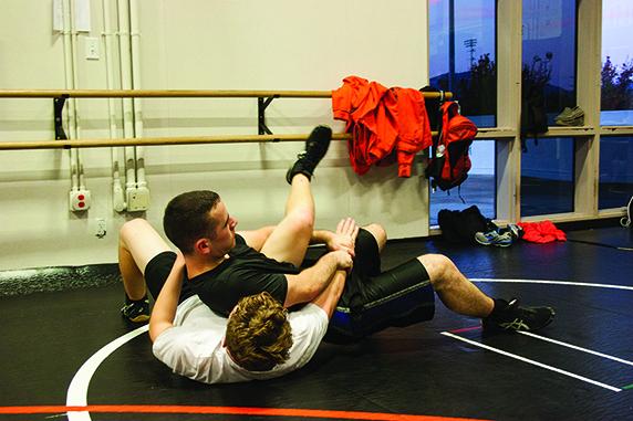 Senior Colton Rettig, on top, wrestles junior Ryan Hurcombe in an early season practice.
