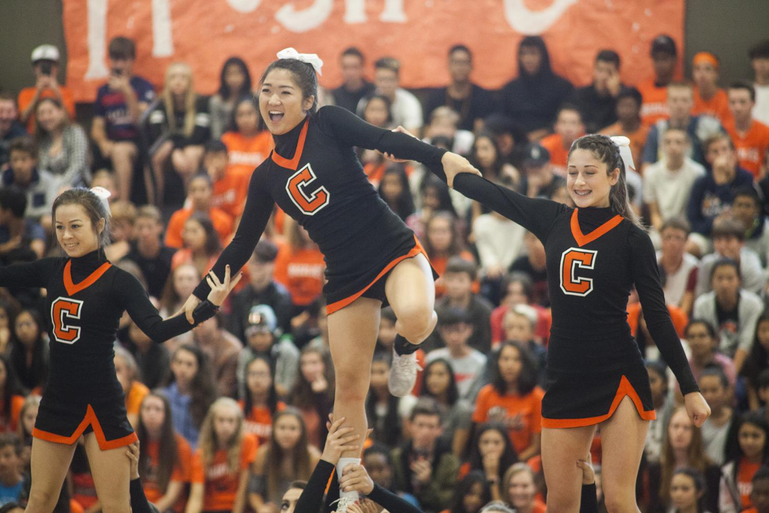 From left to right, sideline cheerleaders Samantha Fredrickson,  Isabelle Yoo, and Taylor Craig perform at the first rally.