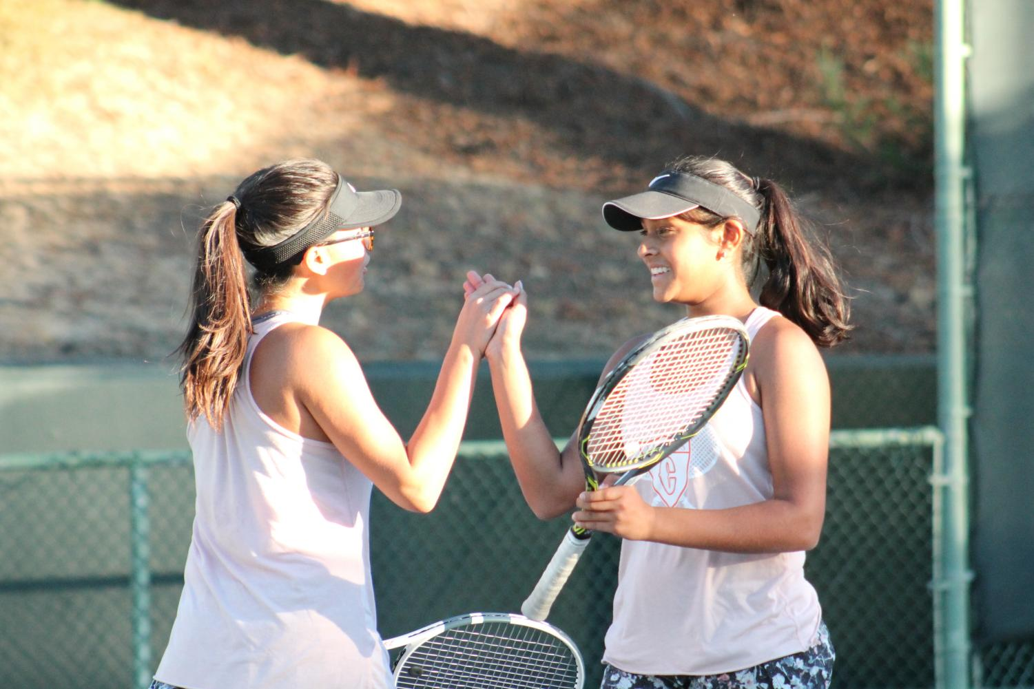 Sophomores Taylor Long, left, and Shrishti Garg celebrate in a match against Amador Valley. The duo won the EBAL Doubles Championship and qualified for NCS.