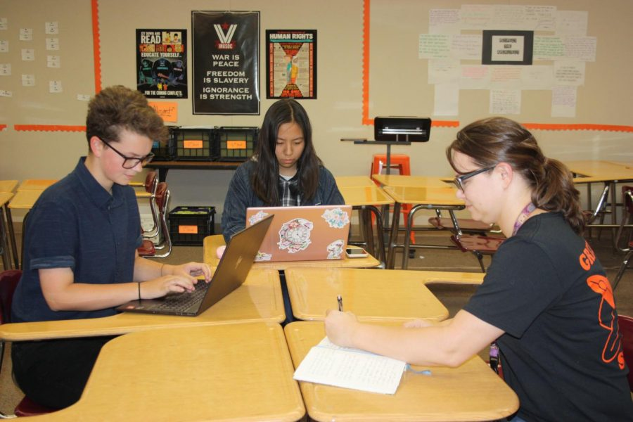 From left to right, students Sam Gilstrap and Caroline Jiang work with English teacher Devan Manning to try write a novel by the end of the month through National Novel.