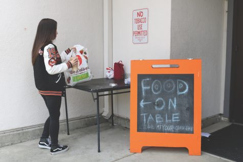 A student picks up her lunch at the food table located outside the front office, where many lunch thefts have occurred.