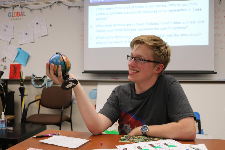 Harvey studies a world globe in geography teacher Hannah Cheng's classroom.