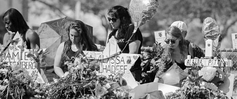 Mourners pay tribute at a memorial for victims at the Marjory Stoneman Douglas High School shooting. Two survivors, Sydney Aiello and Calvin Desir, recently committed suicide.