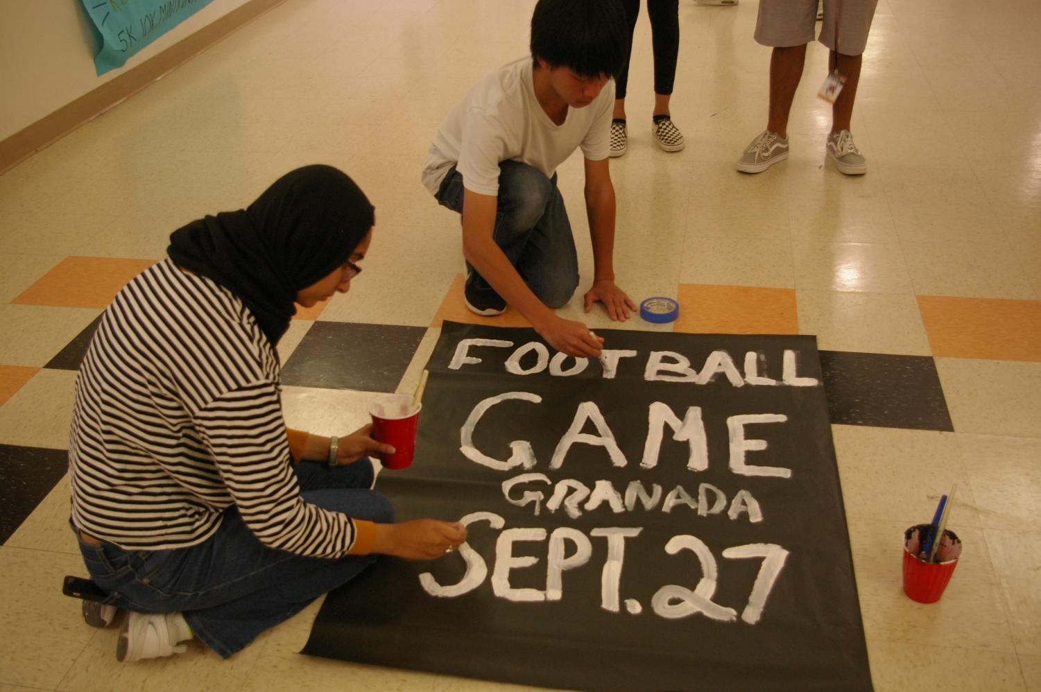 From left to right, freshman leadership students Alizay Iqbal and Christopher Chiang paint a poster to advertise the football game that took place on Sept. 27.