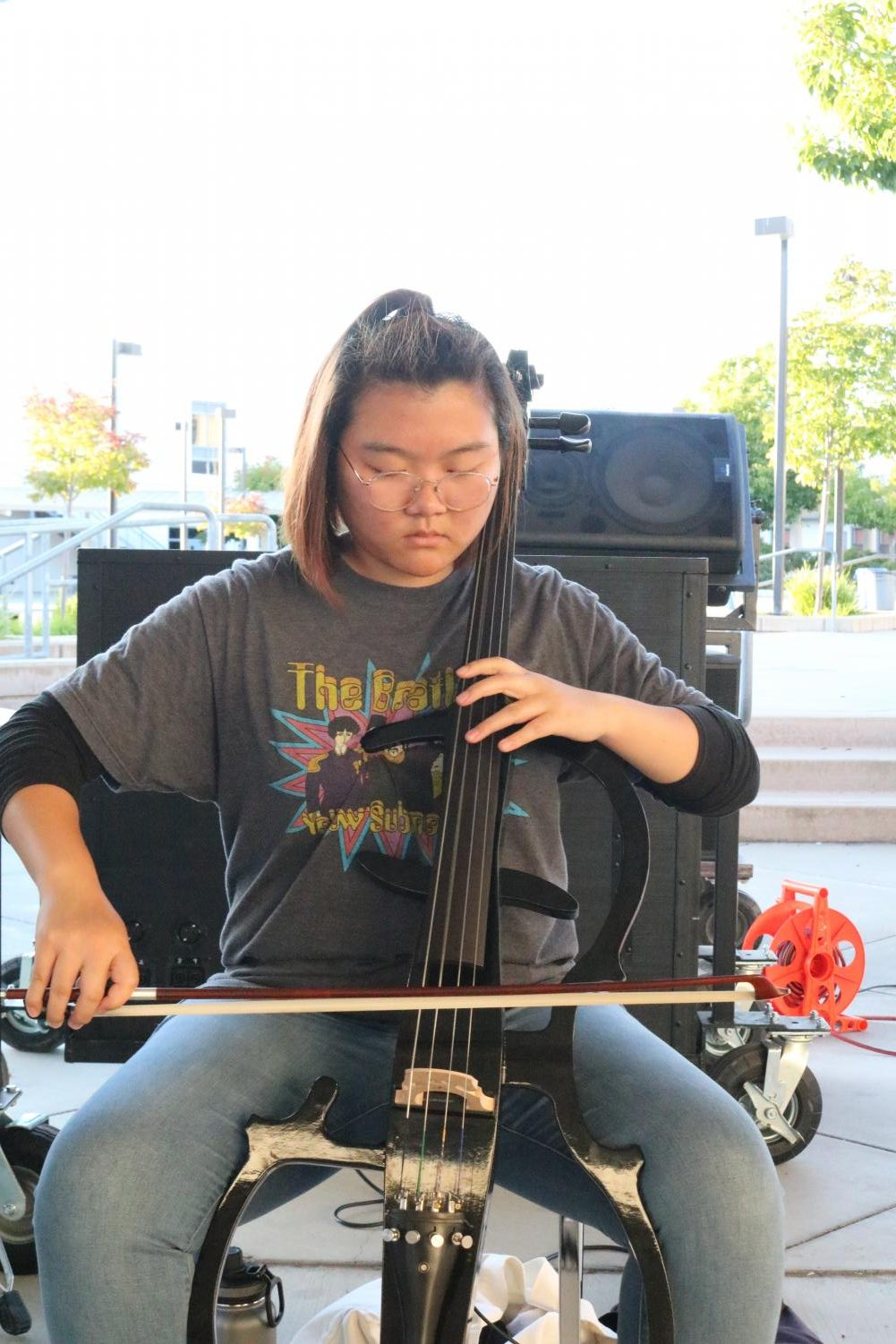 Senior cellist Jewel Cha practices with the marching band. She is the only string player in the band in the last two years.