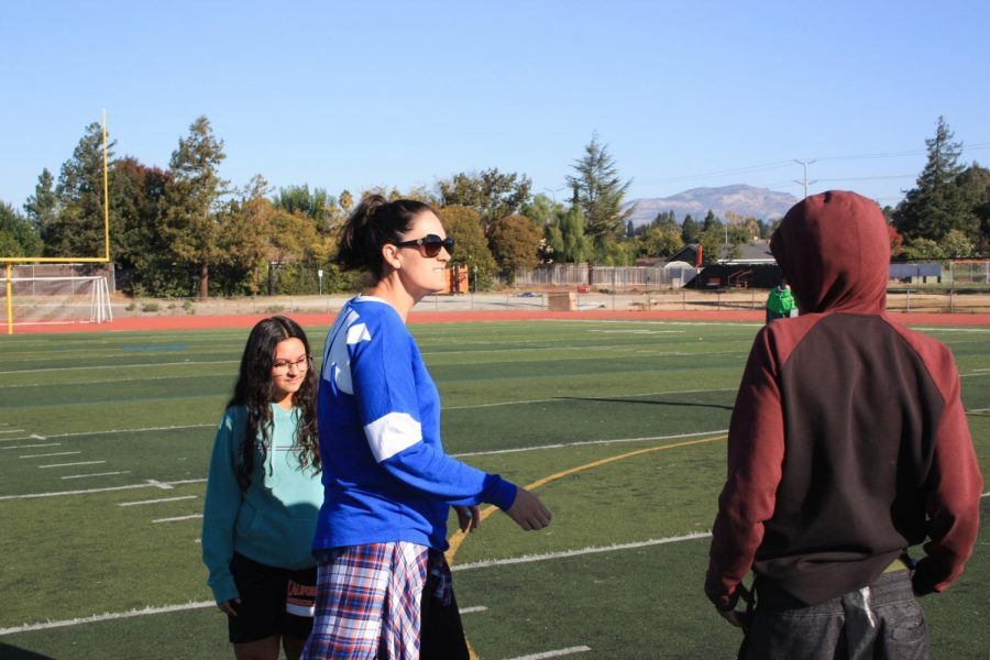 PE teacher Sheridan Kautzmann, left, talks to one of her students during class on the football field.