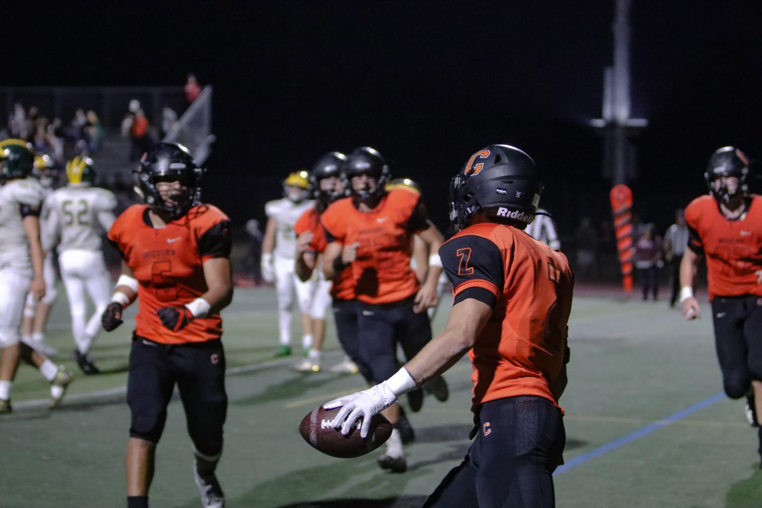 Above, senior Belal Alatasi, right, gets ready to celebrate a touchdown with his unrushing teammates. Unfortunately, the Grizzlies lost the homecoming game on October 25 to San Ramon Valley, 24-21, in the closing seconds of the game.
