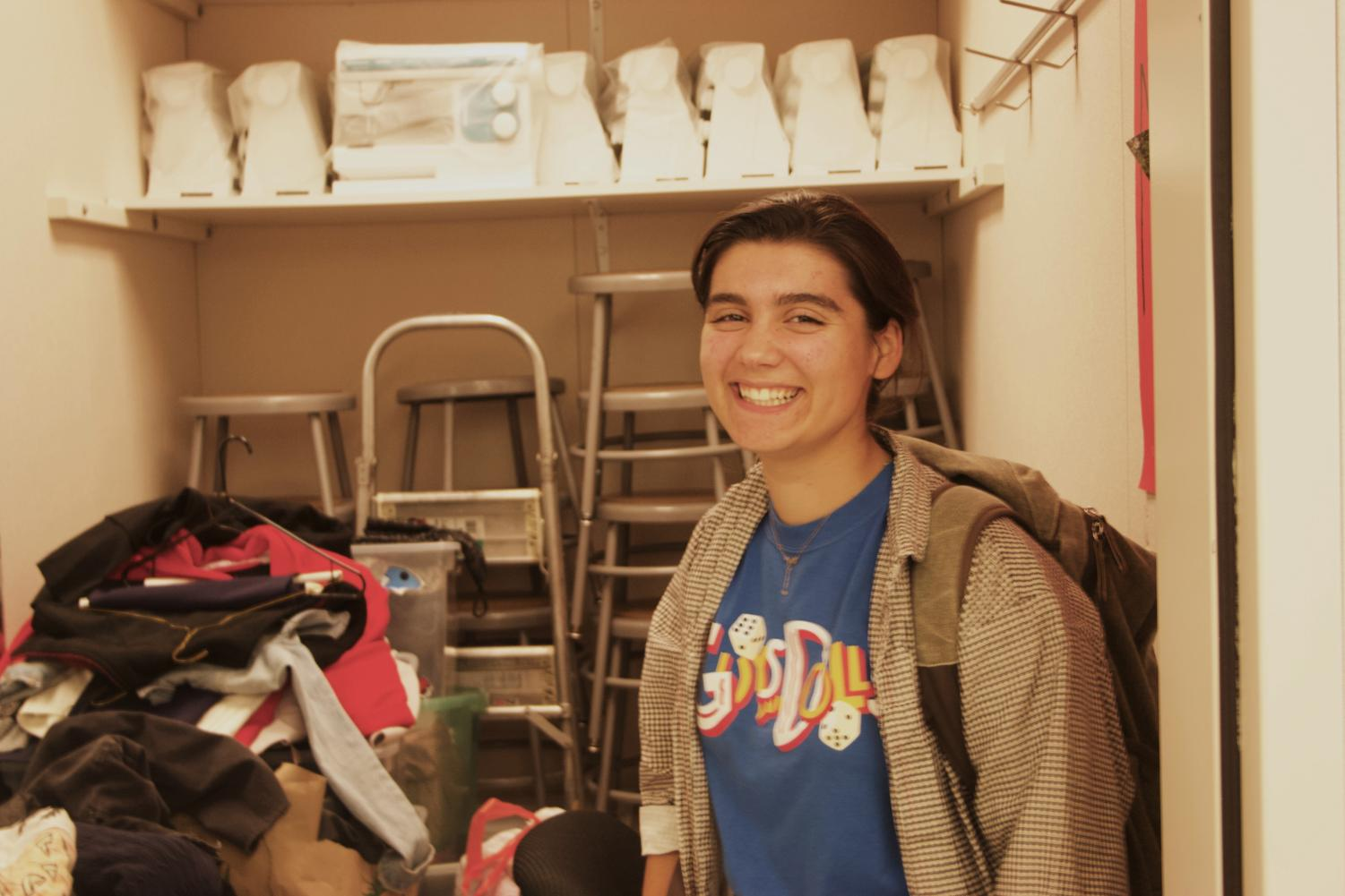 Senior Caelen Chamberlain poses in front of clothes that students donated, in preparation for the clothing swap on Nov. 18-22.