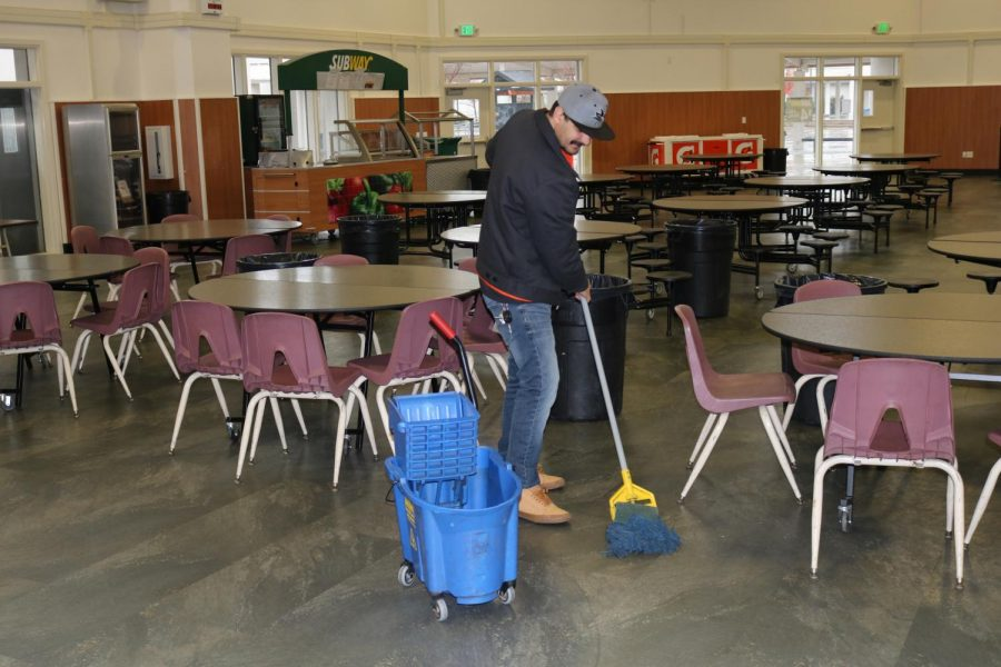 Custodian Ricky Galvao mops the commons floors after lunch. He's one of 13 custodians who work at Cal High.