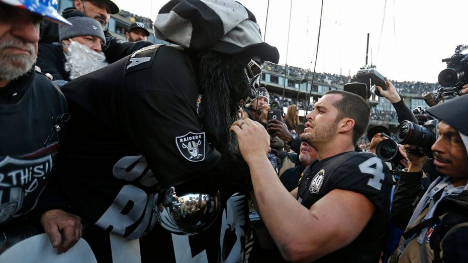 Raiders quarterback Derek Carr greets avid fans as the Raiders are booed off the field in their last game in Oakland. Fittingly, the Raiders lost the game to Jacksonville, 20-16. Photo Courtesy of The Oklahoman.