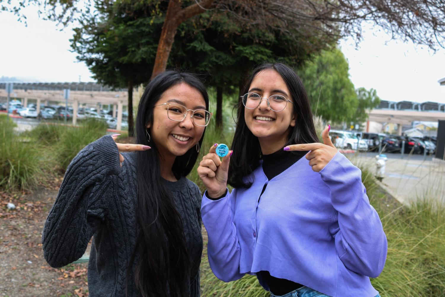 Pin Pals co-presidents and seniors Clarissa Mendoza, left, and Riya Belani pose with one of the pins that their club has designed for Saugus High School in Santa Clarita. Proceeds from pin sales went to support the Southern California school which experienced a shooting on Nov. 14 that killed two students.