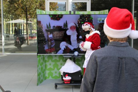 Opinions Editor Nick Harvey waits in the line to virtually meet with Santa Claus Saturday at the City Center. Kids of all ages were able to remotely engage with Santa, who appeared on a large, flatscreen TV. Mrs. Claus was there in person to help out.