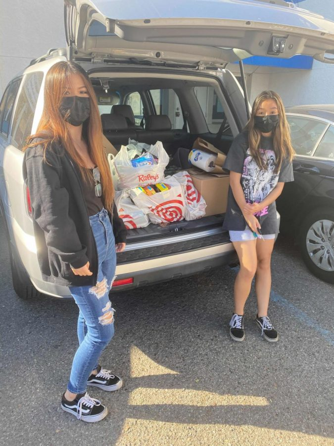 Seniors Audrey Zhang, left, and Kaitlyn Perry helped collect food and other supplies for an Interact service project that benefitted the Bay Area Rescue Mission.