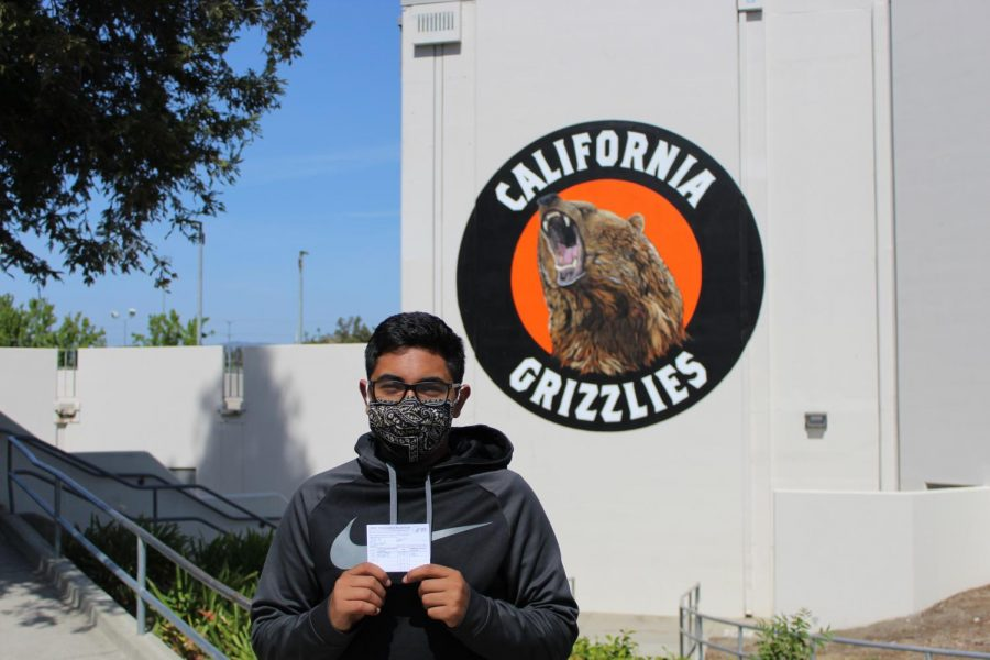 Cal High junior Jonah Aziz stands in front of Cal High holding his COVID-19 vaccination card.