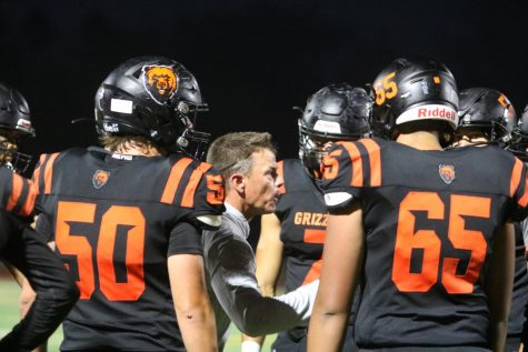 Varsity football coach Danny Calcagno talks with members of his team during Fridays homecoming game, which Cal won 41-7 over MIlpitas. All coaches and athletes are now required by the district to show proof of vaccination or be tested twice a week for COVID-19.